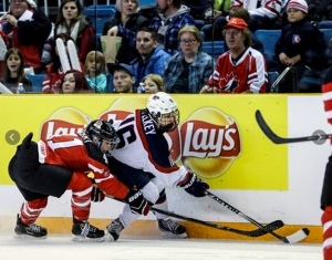 UVM's Amanda Pelkey protects the puck from a Canadian defender at the 2014 Four Nations Cup
